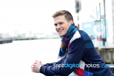 handsome man leaning on railing at river stock photo royalty free