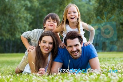 c2eb40d57d5 Happy Young Family Lying On Grass Stock Photo - Royalty Free Image ...