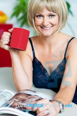pretty woman with a coffee mug in hand reading magazine stock photo royalty free image id. Black Bedroom Furniture Sets. Home Design Ideas