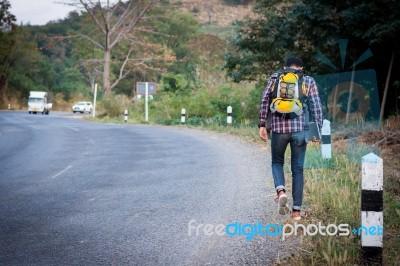 Tourists Man Walk Along Mountain Roads Stock Photo - Royalty