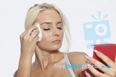 Young Woman Clean Face With Wet Wipes And Holding Mirror Stock Photo ... 27905e402